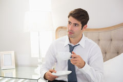 Serious well dressed man with a cup of tea in bed Stock Image