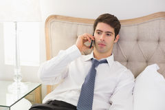 Serious well dressed man using mobile phone in bed Stock Photography