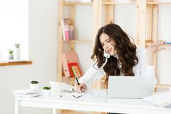Serious well-dressed saleswoman talking on phone in office behind her desk and laptop computer. Copy space.  Stock Photography
