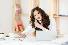 Serious well-dressed saleswoman talking on phone in office behind her desk and laptop computer. Copy space.  stock photo