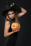 The serious witch is standing with the pumpkin Stock Image