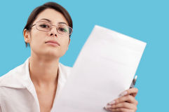 Serious woman. Holding a sheet of paper and a pen on her hand Royalty Free Stock Photos
