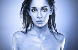 Serious Woman. Horizontal head and shoulders shot of a serious 18 year old woman with no clothes visible.  Blue tint added to overall photograph Royalty Free Stock Images