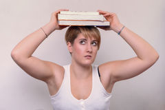 Serious Woman Balancing Books on her Head Stock Photos