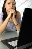 Serious woman behind a laptop Royalty Free Stock Photos
