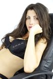Serious woman in bikini sitting on the leather chair of her boss Royalty Free Stock Image
