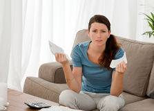 Serious woman with bills on the sofa Stock Photography