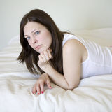 serious woman with blue eyes lying on bed Royalty Free Stock Photo