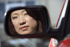 Serious woman in car mirror Stock Image