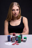 Serious woman in casino with cards and chips Stock Photos