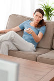 Serious woman changing channel sitting on the sofa Stock Images