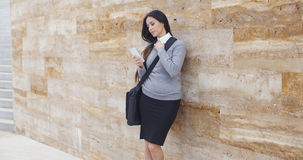 Serious woman checking email on phone outdoors Stock Photo