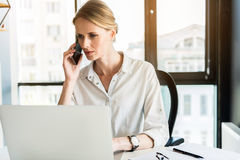 Serious woman is communicating by mobile phone with frustrate Royalty Free Stock Photo