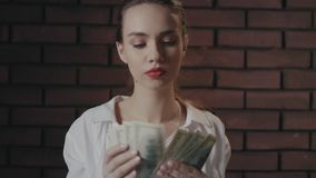 Serious woman counting money banknotes on brick wall. Wealthy businesswoman stock video