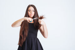 Serious woman cutting splitting ends of her long fragile hair Stock Photo