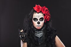 Serious woman in day of the dead mask with gun Royalty Free Stock Images