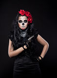 Serious woman in day of the dead mask with gun Royalty Free Stock Photography