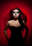Serious woman in day of the dead mask on red. Young woman wearing with roses dressed up for All Souls Day royalty free stock photography