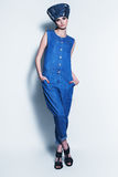 Serious woman in denim hat and jumpsuit Stock Images