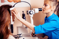 Serious woman doctor checks her eyesight to the patient in the c Stock Images