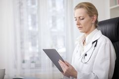 Serious Woman Doctor Holding a Tablet Computer Stock Photography