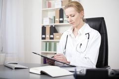 Serious Woman Doctor Reviewing Written Findings Stock Photography