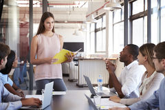 Serious woman with document stands addressing team meeting Stock Image
