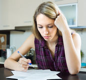 Serious woman with documents in kitchen Stock Photo