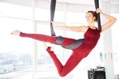 Serious Woman Doing Antigravity Yoga Using Hammock In Studio