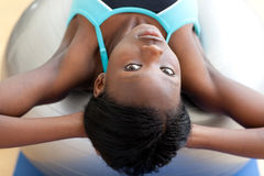 Serious woman doing sit-ups with a pilates ball Stock Photo
