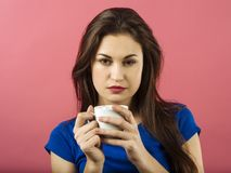 Serious woman drinking coffee over pink background Stock Photo