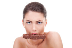 Serious woman eating chocolate bar. Portrait of young serious woman eating chocolate bar over white Stock Images