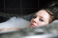 Serious woman enjoys the bath-foam in the bathtub. Stock Photo