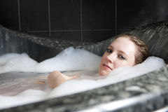 Serious woman enjoys the bath-foam in the bathtub. Royalty Free Stock Photography
