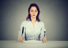 Serious woman with fork and knife sitting at table with empty plate. Serious young woman with fork and knife sitting at table with empty plate  on gray wall Royalty Free Stock Photo