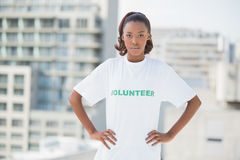 Serious woman with hands on hips wearing volunteer tshirt Stock Photo