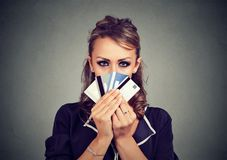 Serious woman hiding face behind many credit cards. Isolated on gray wall background Stock Photos