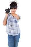 Serious woman holding camera and pointing her finger Royalty Free Stock Images
