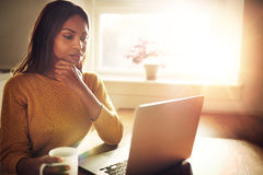 Serious woman holding chin and looking at computer. Serious beautiful woman with hand on chin sitting near bright window while looking at open laptop computer on stock photography