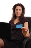 Serious woman holding credit card with laptop Stock Photo