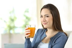 Serious woman holding a glass of orange juice. Sitting on a couch in the living room at home Stock Photo