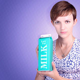 Serious woman holding low fat milk carton Royalty Free Stock Image