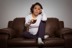Serious woman holding remote control and watching TV Royalty Free Stock Photo