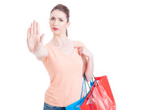 Serious woman holding shopping bags showing stop or hold gesture Stock Image