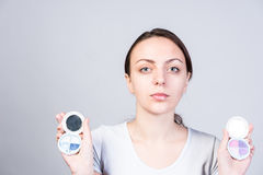 Serious Woman Holding Two Foundation Make-ups Royalty Free Stock Image