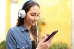 Serious woman listening to music using phone stock photos
