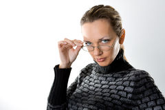 Serious woman looking over glasses. On gray Stock Photo