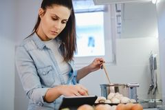 Woman looking at recipe on a tablet and cooking. Serious woman looking at recipe on a tablet and cooking in her kitchen Stock Photo