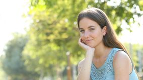 Serious woman looks at camera in a park stock video footage