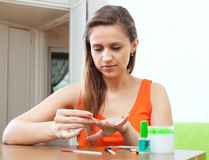 Serious woman looks at nails Royalty Free Stock Photography